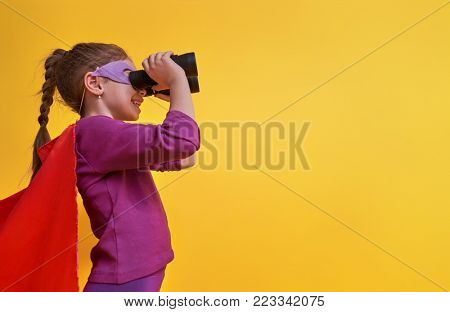 Little child is playing superhero. Kid on the background of bright ultra violet wall. Girl power concept. Yellow, red and  purple colors.