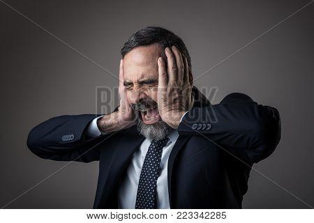 Senior business man having a terrible headache, screaming furiously
