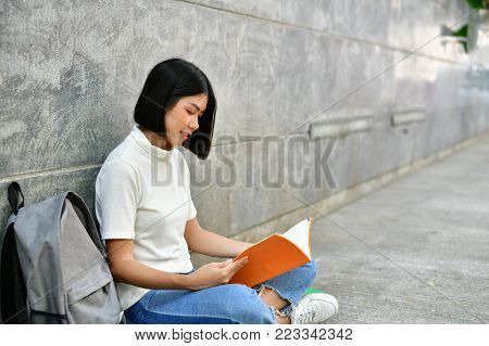 Education Concepts. Asian women reading books in the University. Beautiful women are relaxing in the University. Beautiful women are happy to read. Asian girls love to study. Education of Asian Women.
