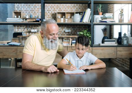 He is so smart. Waist up shot of a joyful senior gentleman grinning broadly while sitting at a table and doing a home assignment with his grandson.