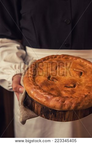 Pie from potato meat cheese and vegetables. Freshly baked pie in hands of woman in uniform