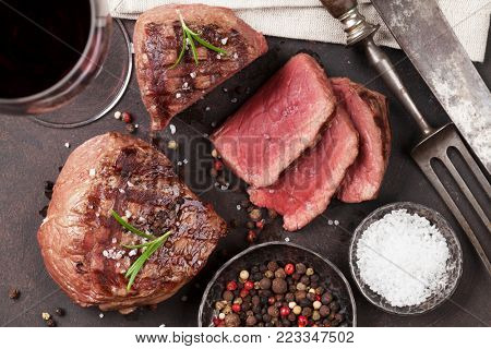 Grilled fillet steaks on cutting board and glass of red wine. Top view