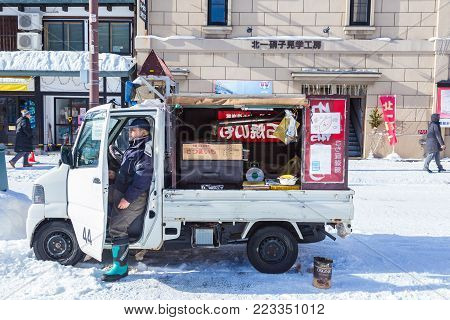 Otaru, Hokkaido, Japan - 30 December 2017, Baked sweet potato food vendor man waits patiently at his converted grilled mini truck for customers to buy his baked sweet potatos in Otaru, Hokkaido, Japan on a cold winter day of December 30, 2017