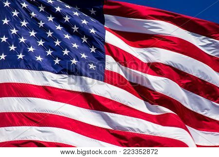 Perfect American Flag waving in the wind with Perfect sunshine along the ripples in the flag. Stars and Stripes of The Patriotic American Flag for USA a symbol of Freemdom
