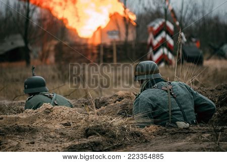 Two German soldiers Wehrmacht run in the trench against the backdrop of a burning house in the village