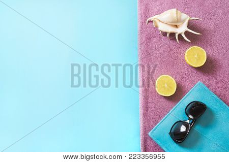 Beach towel, sunglasses and summer accessories on blue background. Travel concept. View from above. Blank mock up for advertising or packaging.