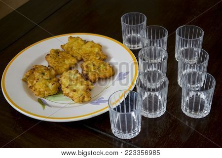 battered and fried potato fritters with some small glasses