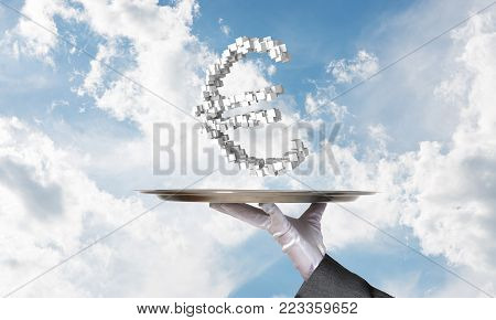 Cropped image of waitress's hand in white glove presenting multiple cubes in form of euro sign on metal tray with cloudy skyscape on background.