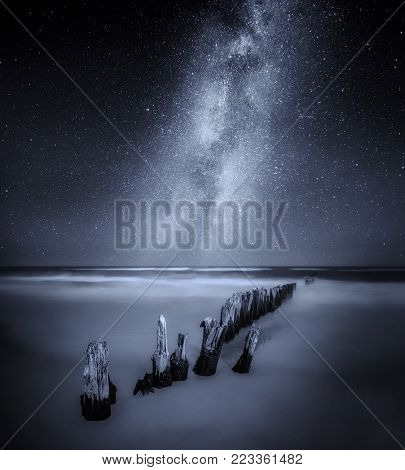 Sea night landscape with Milky Way over old wooden  pier. Fine art landscape.