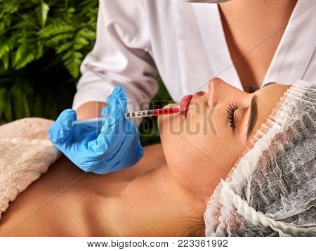 Filler injection for female face. Plastic aesthetic facial surgery by doctor in beauty clinic. Beauty woman giving injections. Green fresh plants in background.