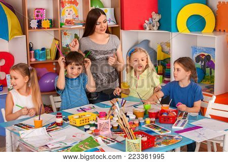 Kids playroom organization of children painting and drawing in kid's club. Craft lesson in primary school. Kindergarten teacher and students work together. Teacher is unhappy with children.