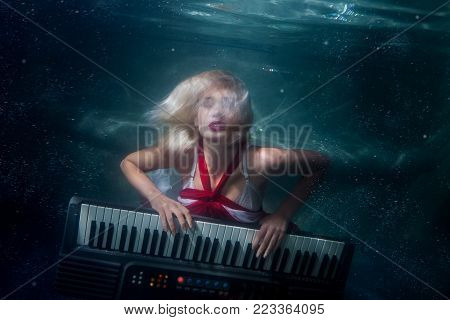 Woman plays music diving under the water, she plays an electric synthesizer.