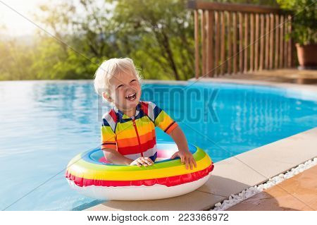 Baby In Swimming Pool. Kids Swim. Child Summer Fun.