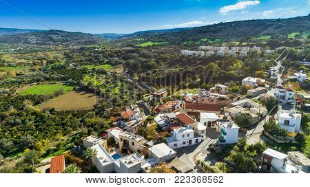 Goudi village, Paphos, Cyprus - 12/26/2017: Aerial bird eye view of Polis Chrysochous valley. View of traditional ceramic tile roof houses, church, trees, hills and Akamas - Latchi beach bay from above.