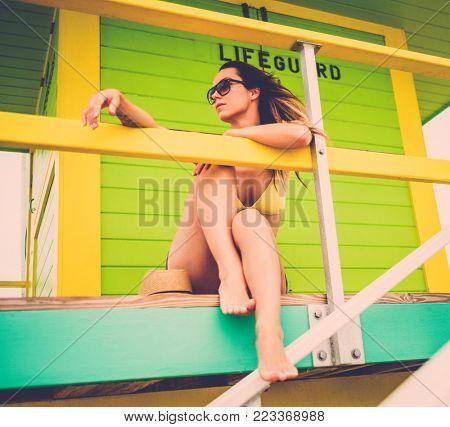 Beautiful woman in bikini at the lifeguard station, Miami, USA.