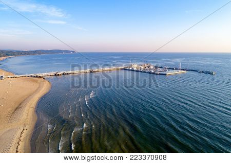 Sopot resort in Poland. Wooden pier (molo) with marina, yachts, pirate tourist ship and beach, Far view of Gdynia.  Aerial view at sunrise.  Sopot resort in Poland. Wooden pier (molo) with marina, yachts, pirate tourist ship,  beach, old lighthouse, churc
