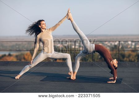 Two Beautiful Women Doing Yoga Asana On The Roof Outdoors