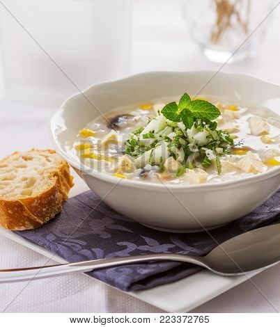 A bowl of rice, chicken and corn soup served with raw onions, parsley and mint leaves.