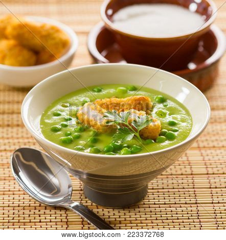 A bowl of green pea soup, served with battered fish.