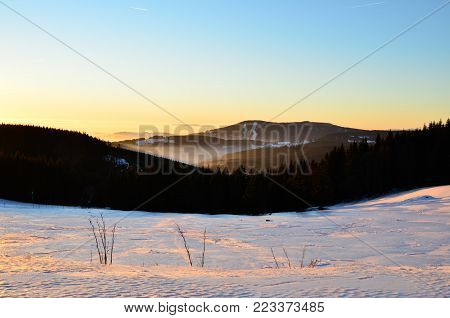 Beautiful sunset in winter over the mountains in Giant Mountains, Czech Republic. Scene with clear blue sky and backlight