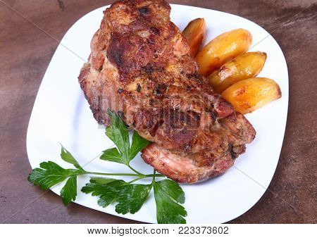 Juicy pork neck chops are grilled with potatoes on a white plate