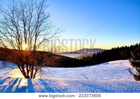 Beautiful sunrise in winter over the mountains. Scene with clear blue sky and backlight