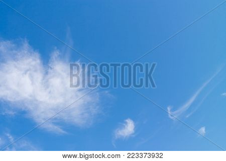 White large fluffy rounded cloud  and small cloud as a checkmark on bright blue sky.