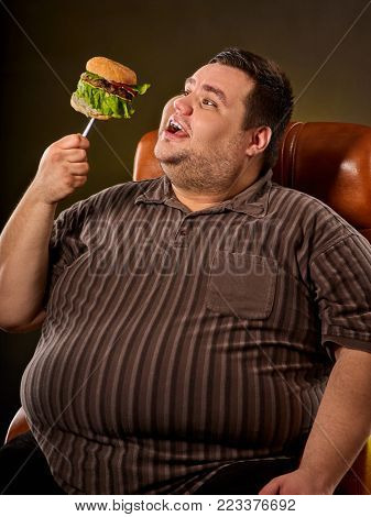 Diet failure of fat man eats fast food hamberger. Happy smile overweight person who spoiled healthy food by eat huge hamburger on fork. Man rejoices at end of diet. Eating junk food.