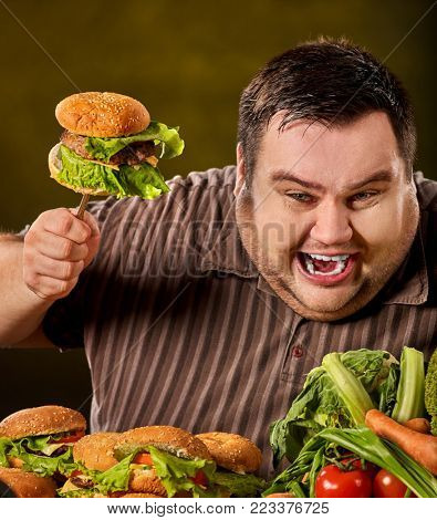 Fat man eating fast food hamberger. Breakfast for overweight person. Junk meal leads to obesity. Person regularly overeats concept on green background. Unhealthy food processing eating.