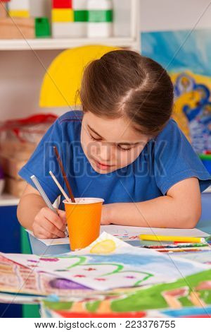 Small students painting in art school class. Child drawing by paints on table. Kid on balloons background. Top view of girl in kindergarten. Development of persistence in small children.
