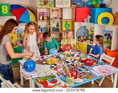 Kids playroom organization of children painting and drawing in kid's club. Craft lesson in primary school. Home kindergarten teacher and students work hobbies together.