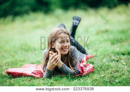 Little Girl In Pink Jacket Lying On Grass, Looking To Camera
