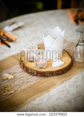 candles in the interior. home decor. candle and pine cones. Decorative white candles stand on a slice of wood. the country house decor is in the details.white - pink heather in autumn basket. wedding