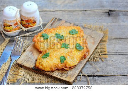 Chicken breast in batter. Fork and knife on an old wooden table. Home crispy fried chicken breast. Batter fried chicken recipe. Rustic style