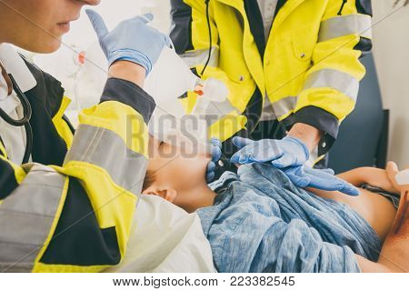 Emergency doctor giving cardiac massage for reanimation in ambulance to woman