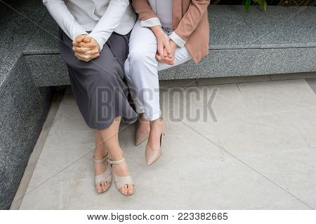 Cropped view of two elegant women sitting on parapet outdoors with their hands clasped. Women friendship concept. High angle view.