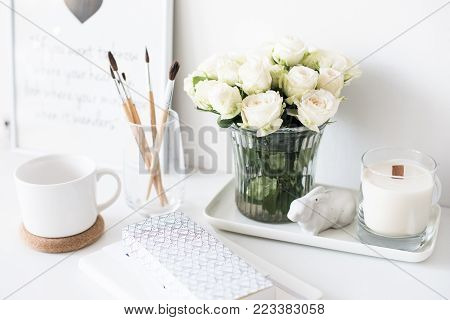 White interior decor with new hand-made candle and bouquet of fresh roses, luxury home decorations in daylight closeup