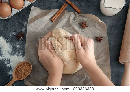 Woman kneading dough on table, closeup