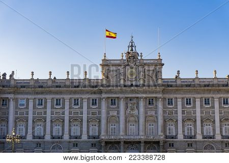 Madrid, Spain Royal Palace facade with Spanish flag waving. External view of Palacio Real de Madrid in the Spanish capital, the official residence of the Spanish Royal Family.