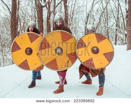 A group of armed medieval warriors are guarded with shields, swords, spears in the winter forest