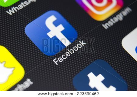 Sankt-Petersburg, Russia, January 24, 2018: Apple iPhone 8 with Facebook icon on monitor screen. Facebook one of the biggest social network website. Icon of Facebook.com on smartphone