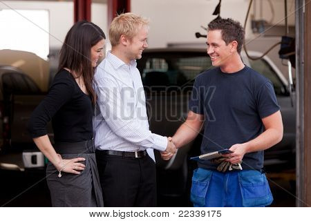 A happy attractive mechanic shaking hands with a customer couple,happy with their service