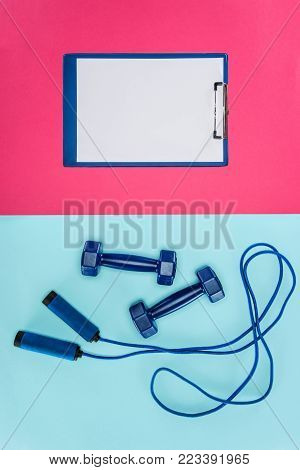 Sports dumbbells, clipboard and skipping rope isolated on pink and blue