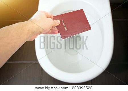 The hand holds the citizen's passport over the toilet, throw out his passport. The concept of change of citizenship, loss of passport, political problems, infringement of rights
