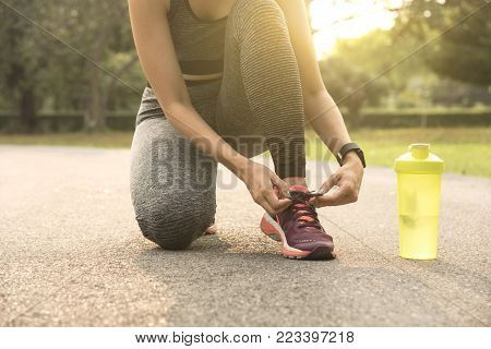 Runner women tie running shoes ready for jogging. Healthy lifestyle concept.