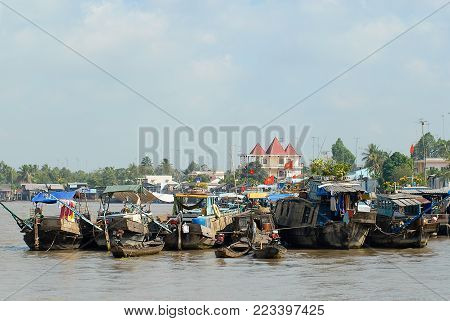 CAI BE, VIETNAM - FEBRUARY 16, 2007: View to the boats floating on water at the famous floating market in Cai Be, Vietnam. Cai Be is often called Venice of Indochina.