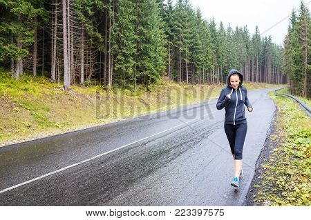 Young sporty woman jogging on mountain road. Running fitness girl in sportswear outdoor image with copy space