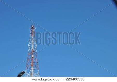 Close up top of communication Tower with antennas such a Mobile phone tower, Cellphone Tower, Phone Pole etc stand on the mountain on white sky background.