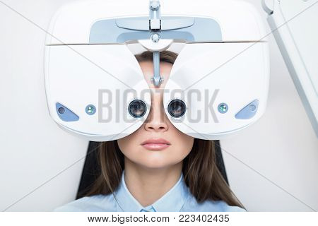 patient woman having her eyes examined with phoropter, face close -up