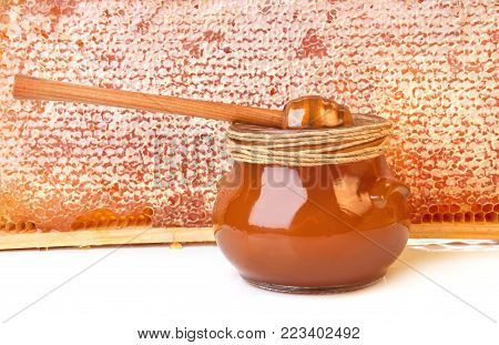Glass jar of fresh honey with honeycomb and wooden spoon